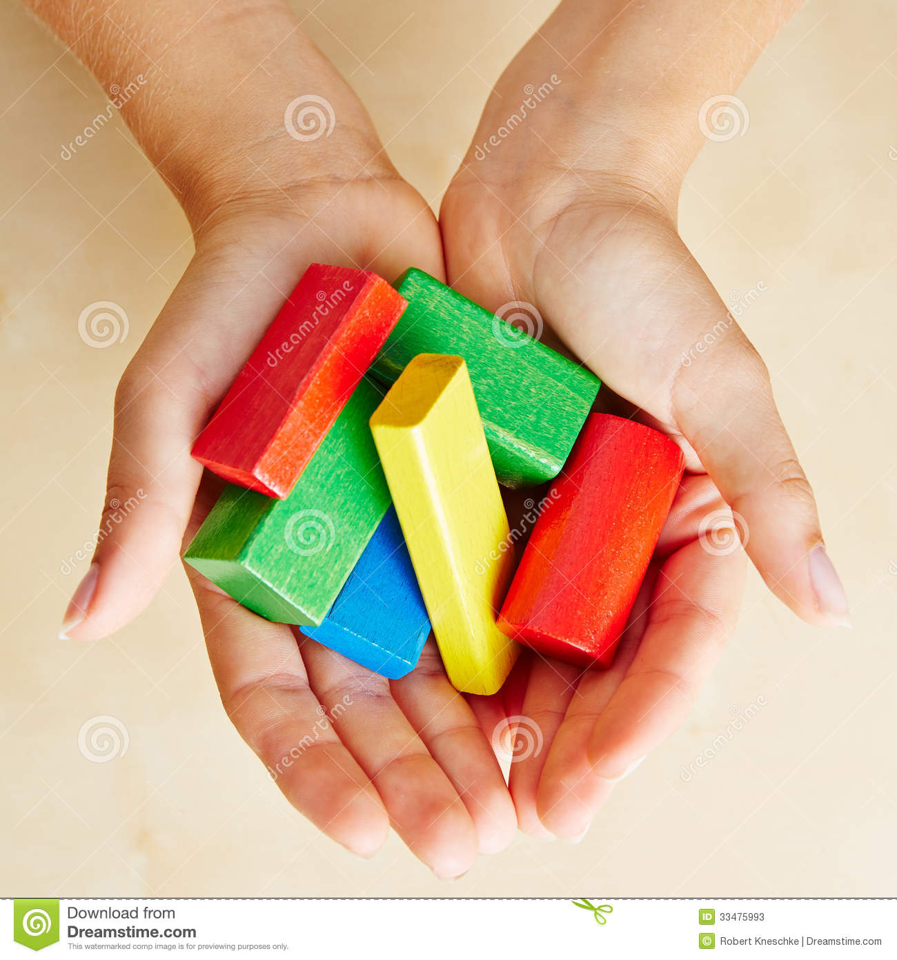 Hands from above holding building blocks
