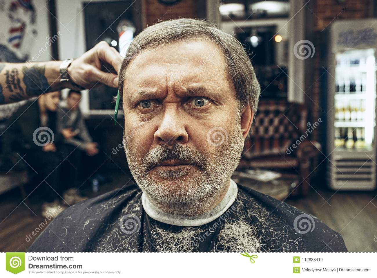 The Hands Of Barber Making Haircut Attractive Old Man In Barbershop