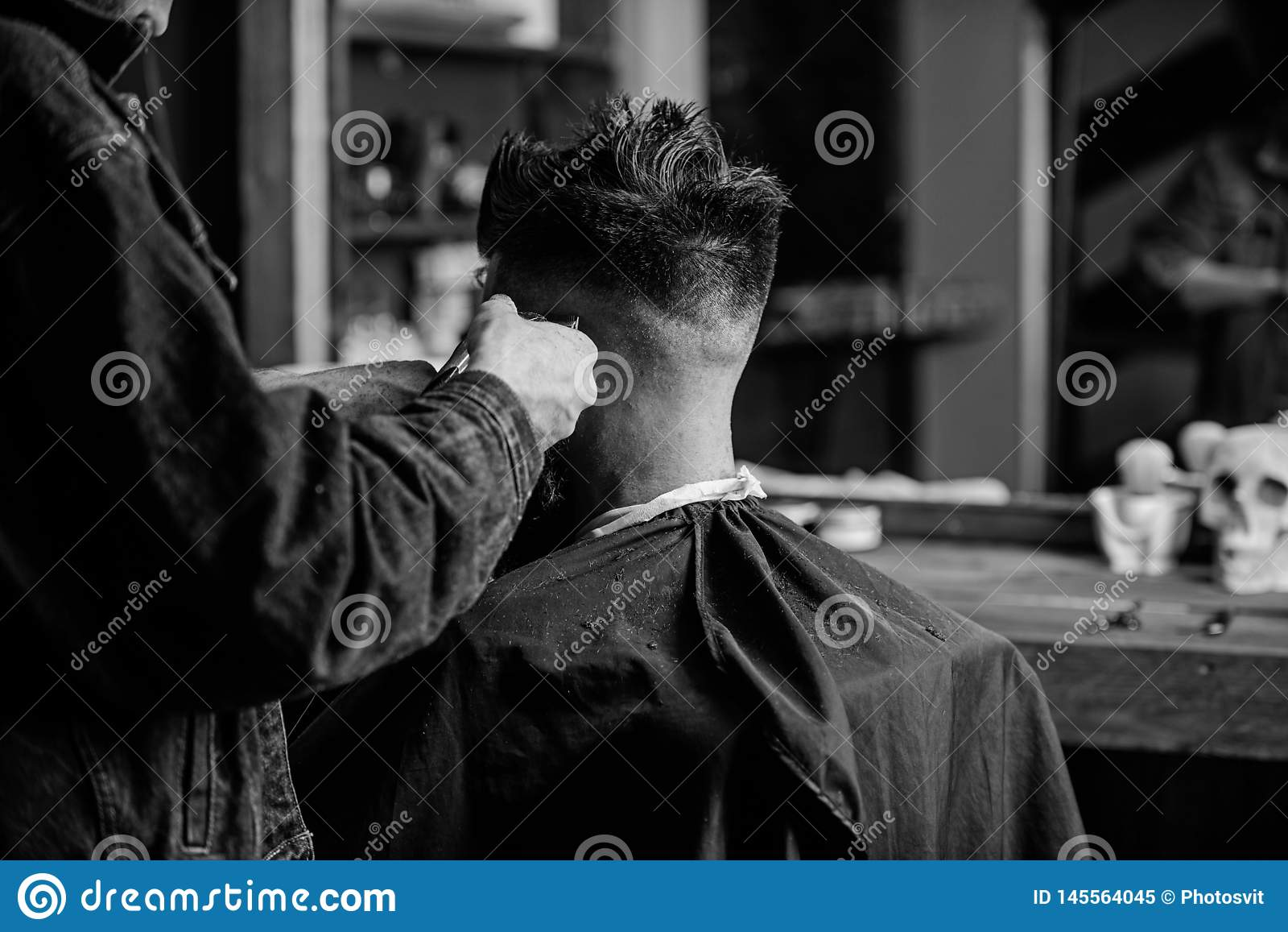 Hands of barber trimming hair of bearded guy with clipper and comb, close up rear view. Barbershop concept. Man with