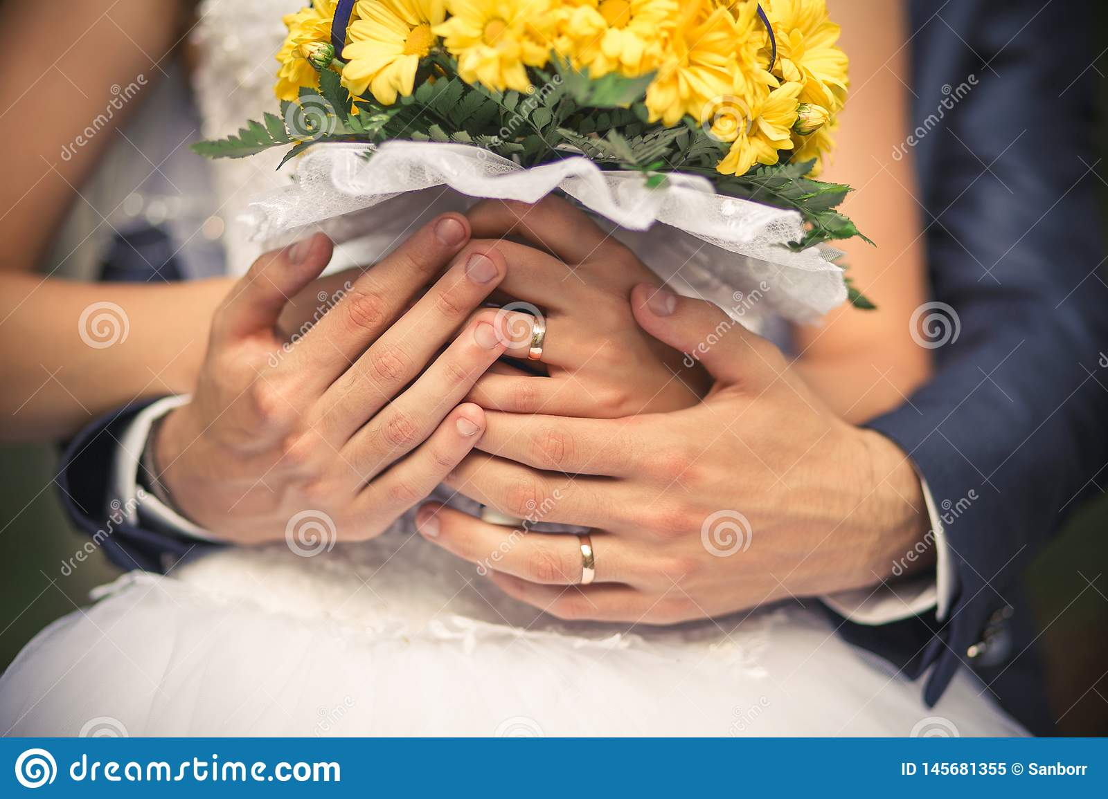Hands of the bride and groom close-up. They have wedding rings on their fingers. The bride is holding a beautiful yellow bouquet
