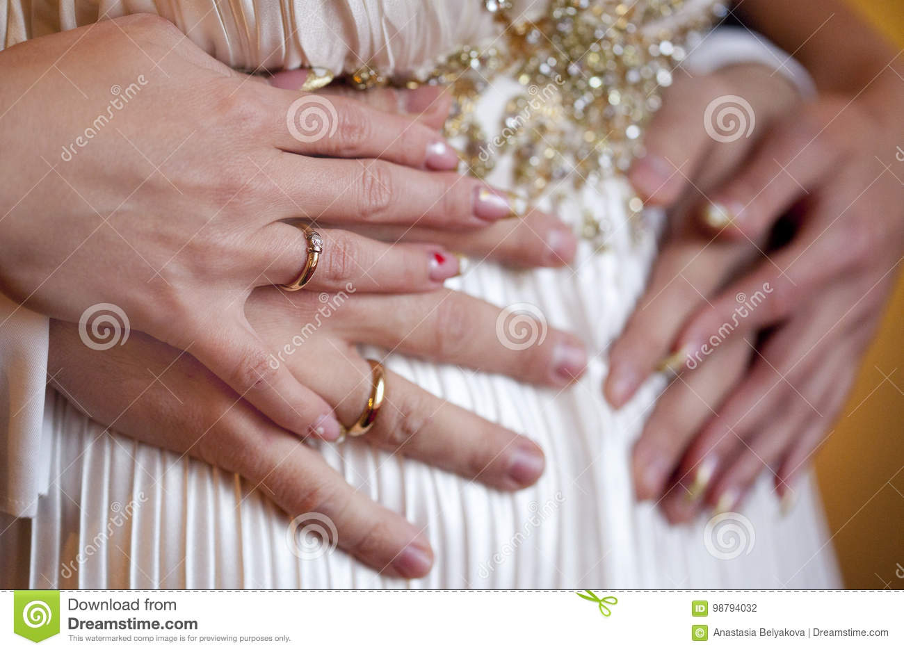 Hands Of Bride And Groom With Wedding Rings On Silk Dress Of Bride ...