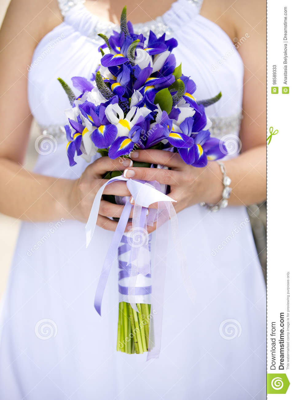 Hands Of Bride Holding Wedding Bouquet Of Violet And White Flowers