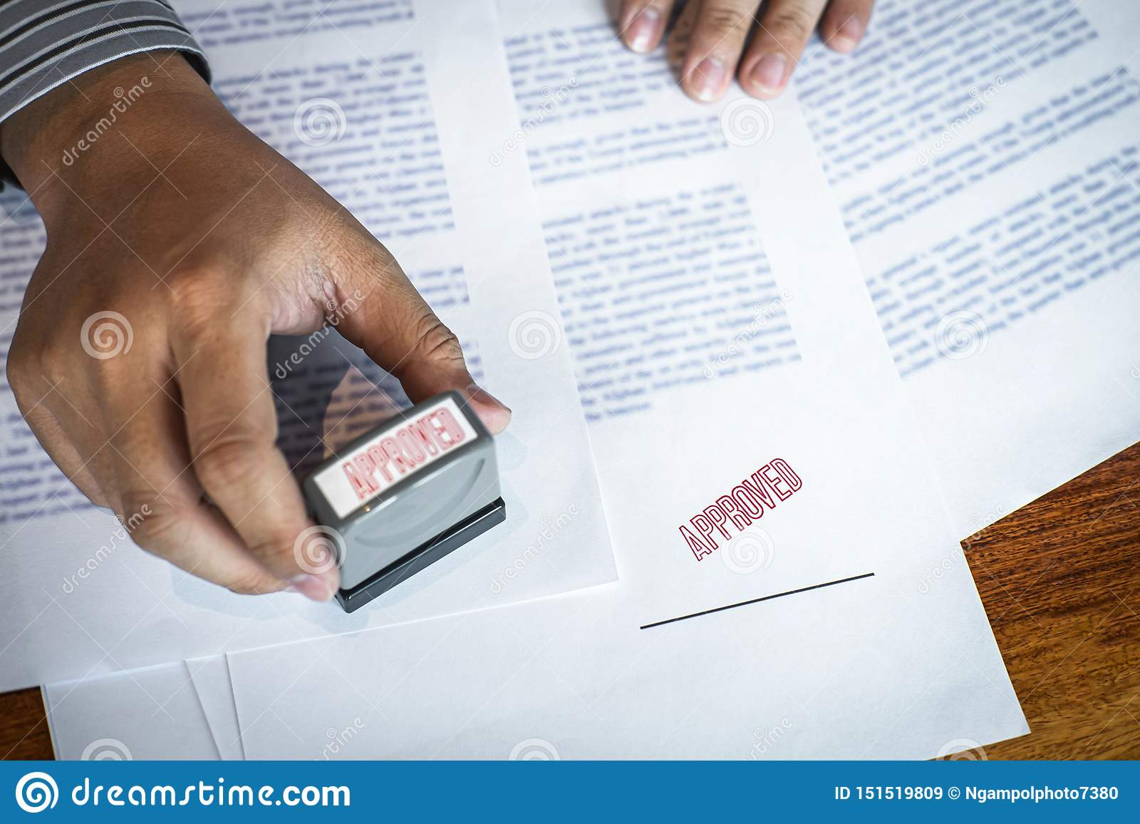 Hands of businessman stamp on paper document to approve business investment contract agreement