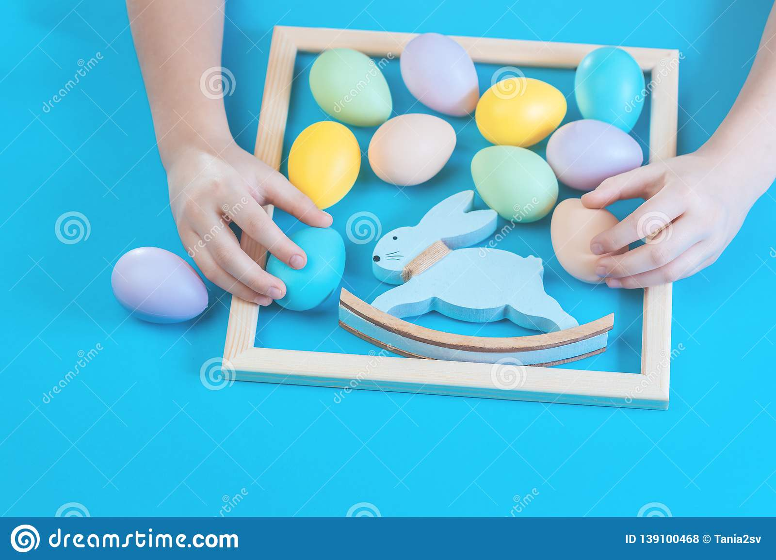 Pastel scattered Easter eggs with kids hands