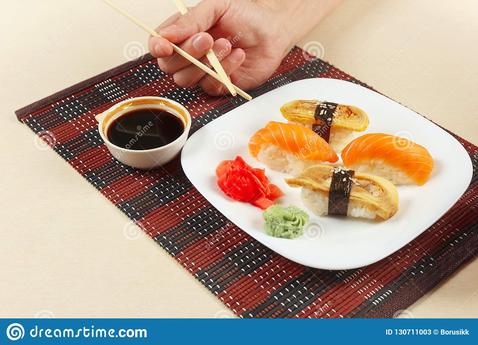 Hands With Chopsticks And Sushi With Omelet With Eel And