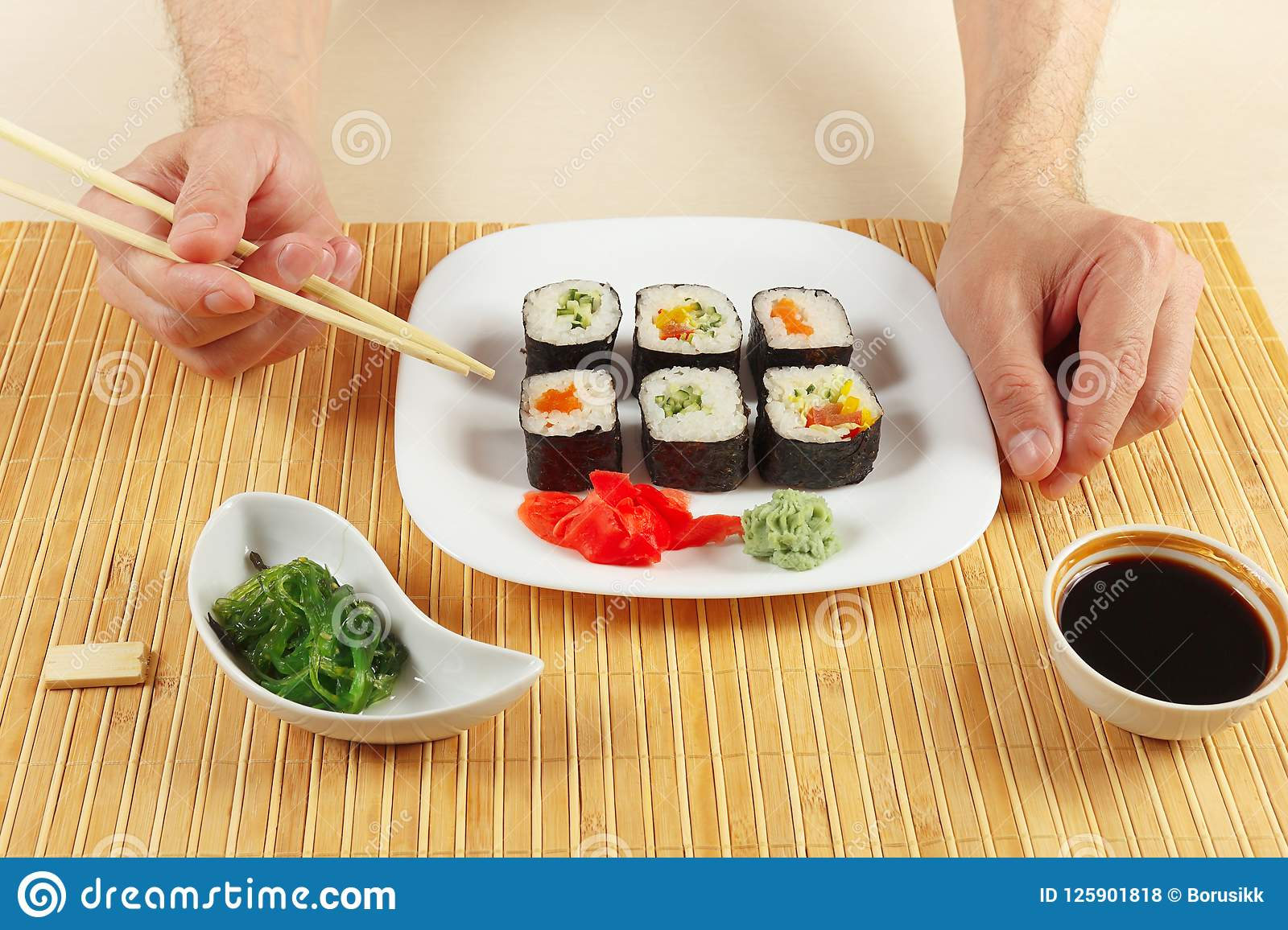 Hands With Chopsticks And Sushi Set Chuka Salad And Soy