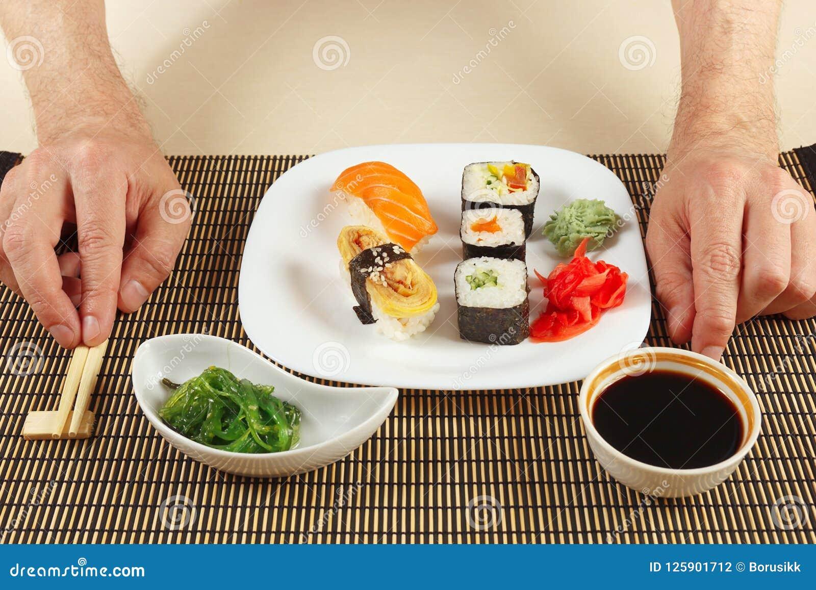 Hands With Chopsticks And Sushi Set Hiyashi Wakame Salad
