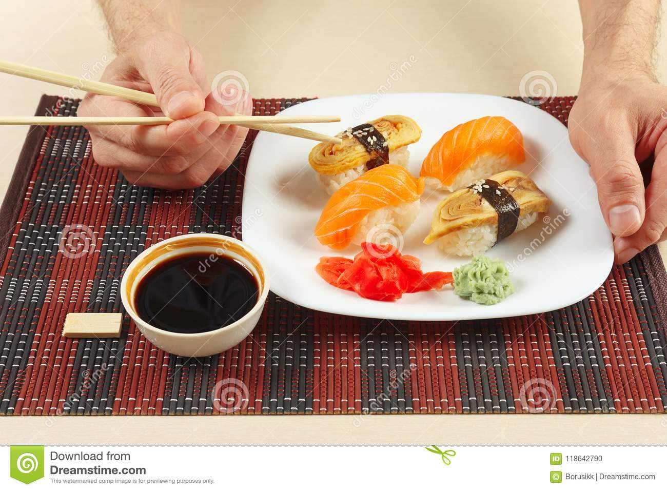 Hands With Chopsticks And Sushi Set And Soy Sauce On Black