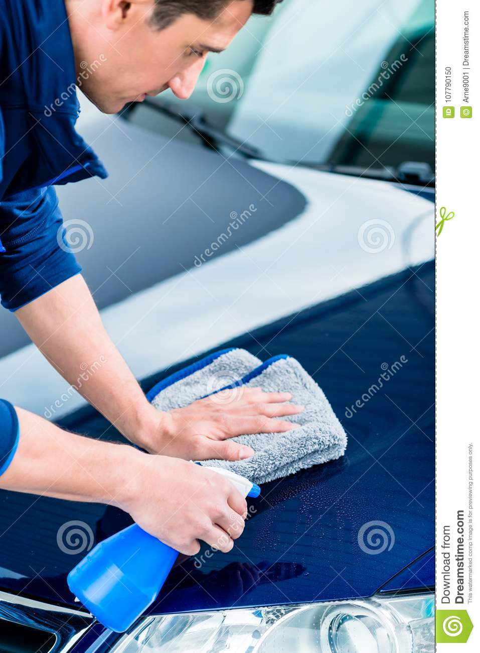 Hands cleaning car with spray cleaner and microfiber towel