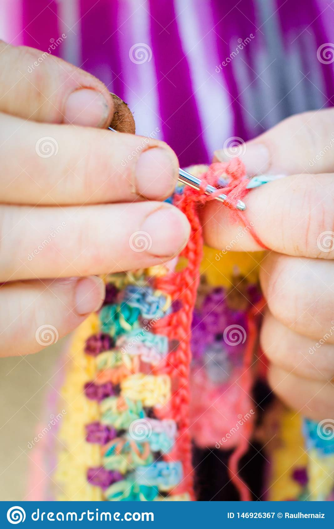 Hands close-up of an old lady knitting on knitting needles, using colorful wool