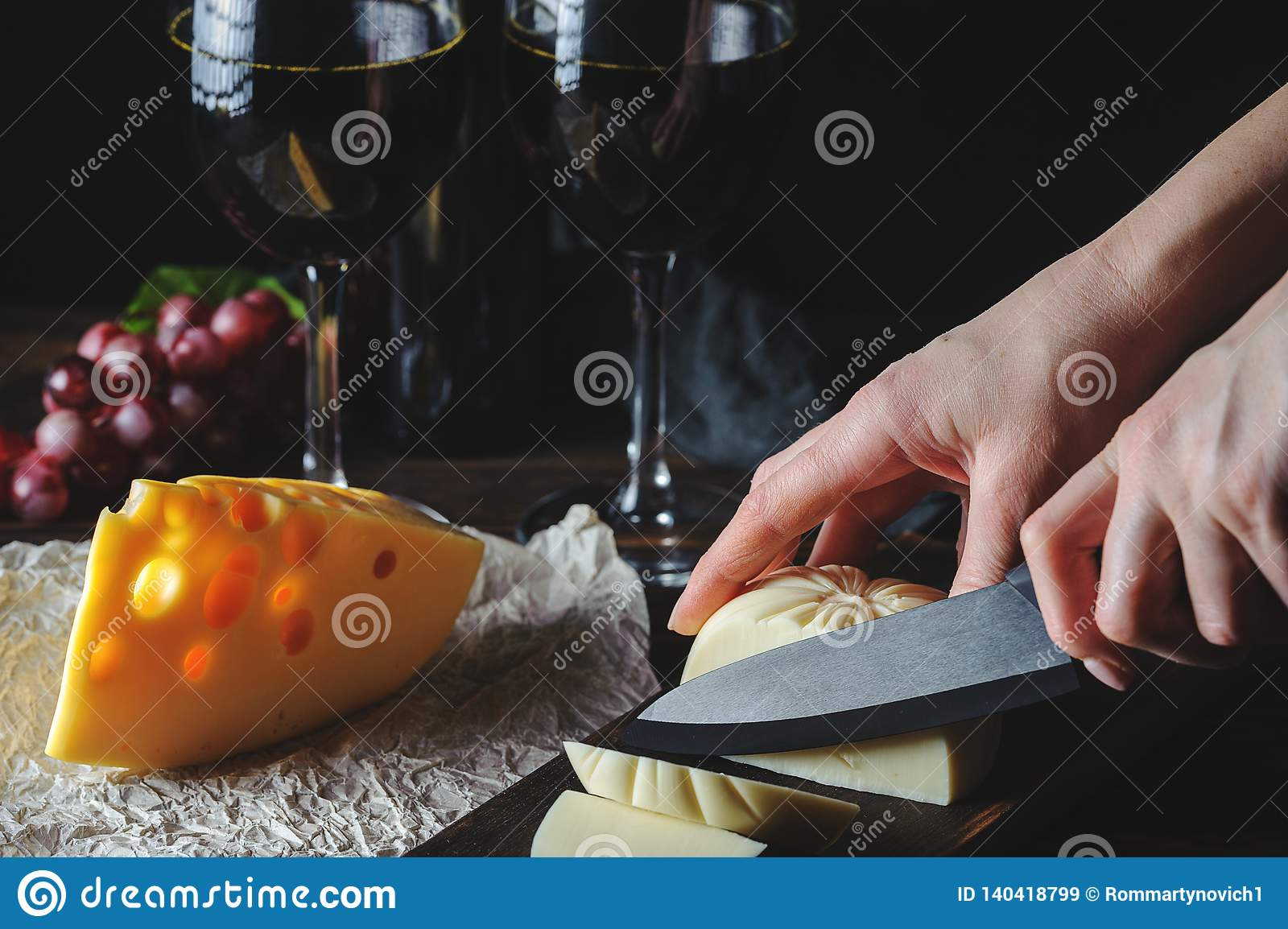 Hands cut the cheese to wine