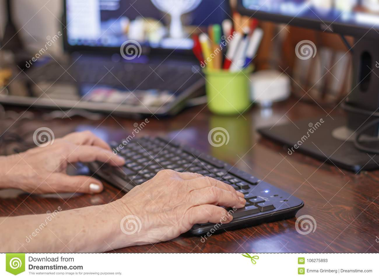 Hands of an elderly woman typing on a pc keyboard