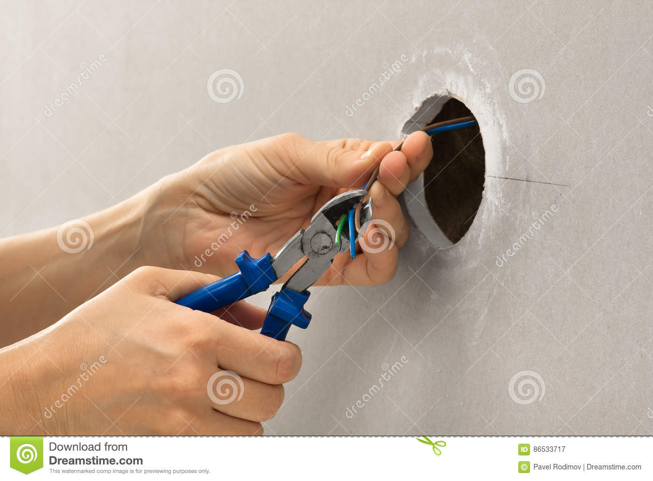 Hands of electrician with wire cutter
