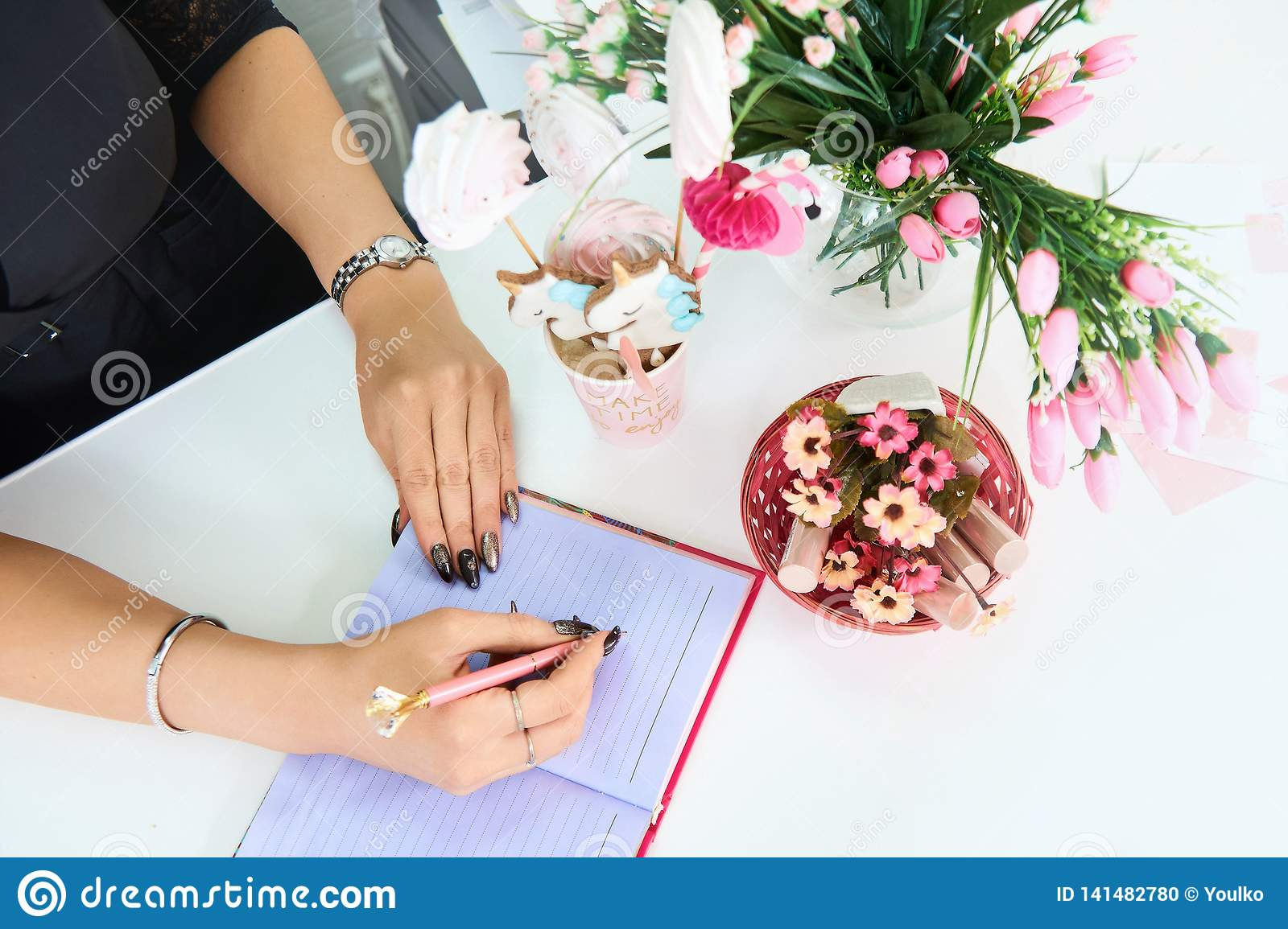 Hands European girls holding a pen and write in an empty notebook. Nearby are flowers and candy