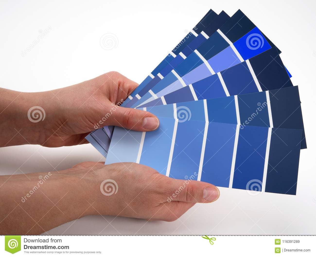 Hands fanning out a selection of a variety of blue colour swatches.