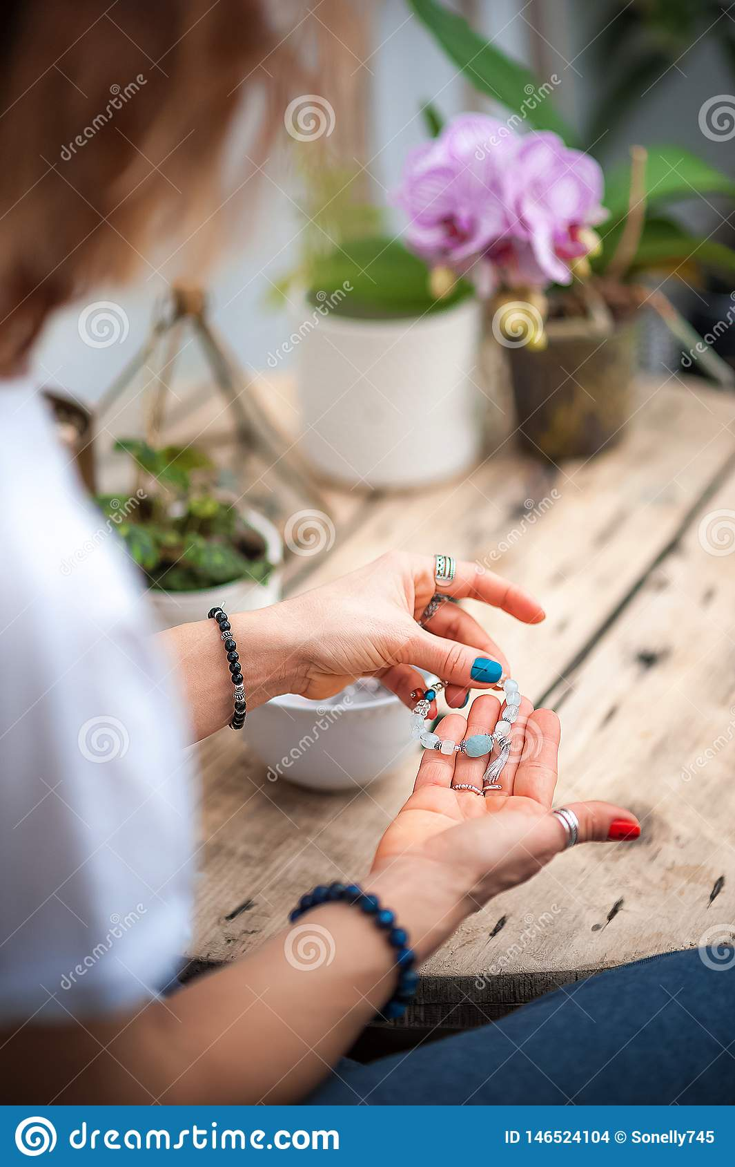The hands of the girl touch the handmade jewelry. Girl and jewelry. Handmade woman decorating stones close up