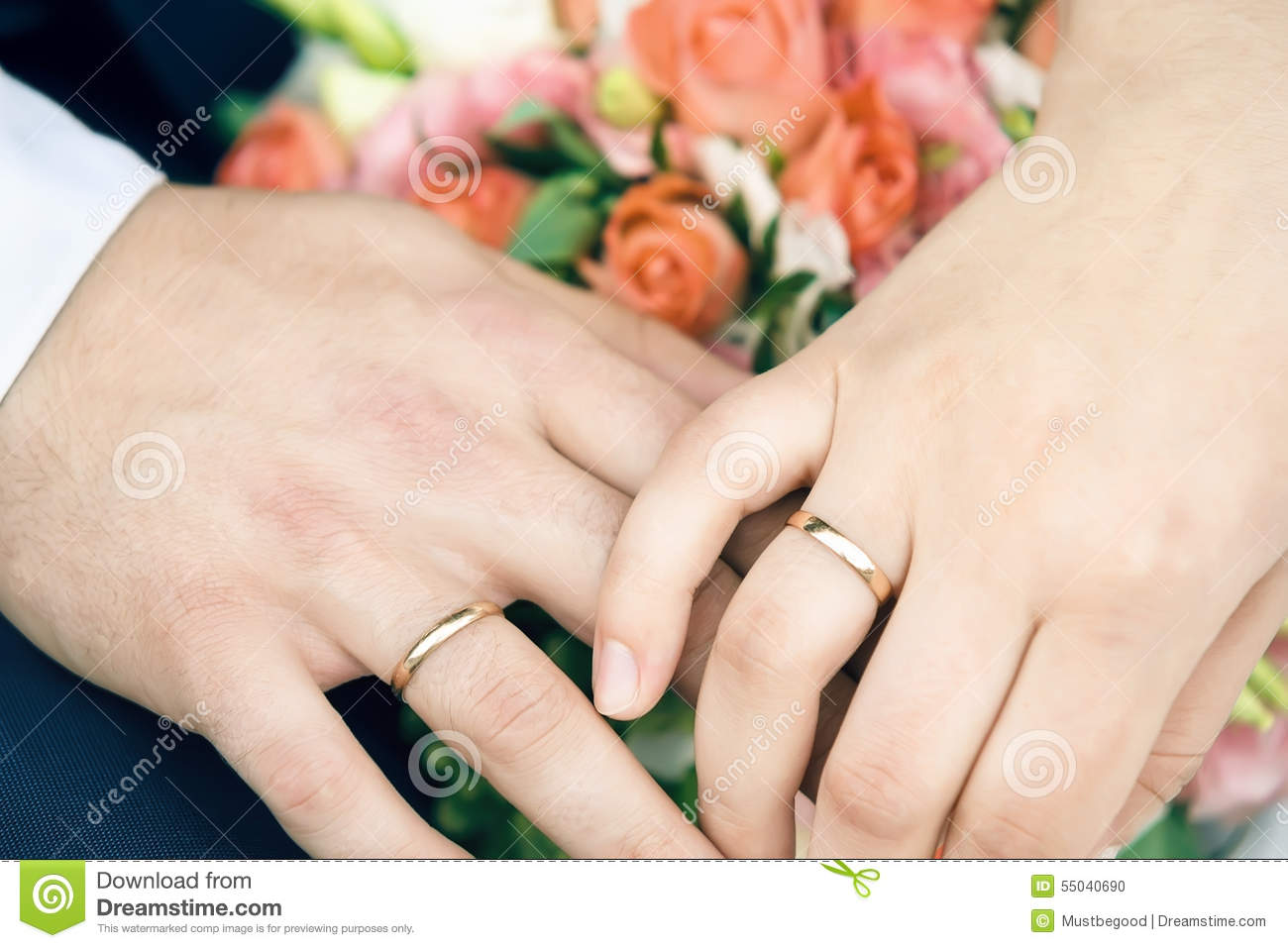 Hands Of Happy Newly Married Couple With Gold Wedding Rings And