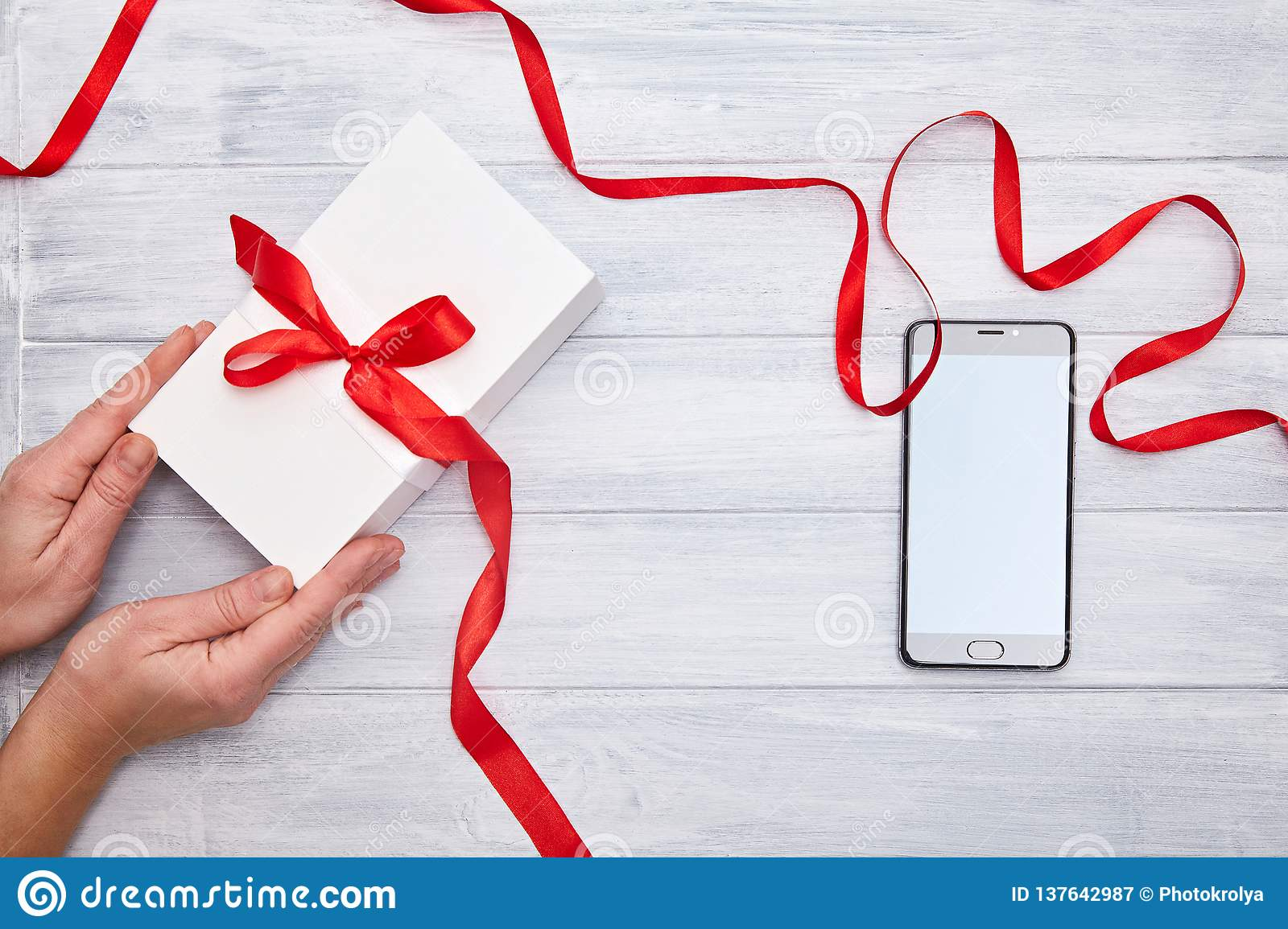 Hands hold Gift Box with red ribbon and smartphone on a woodem background