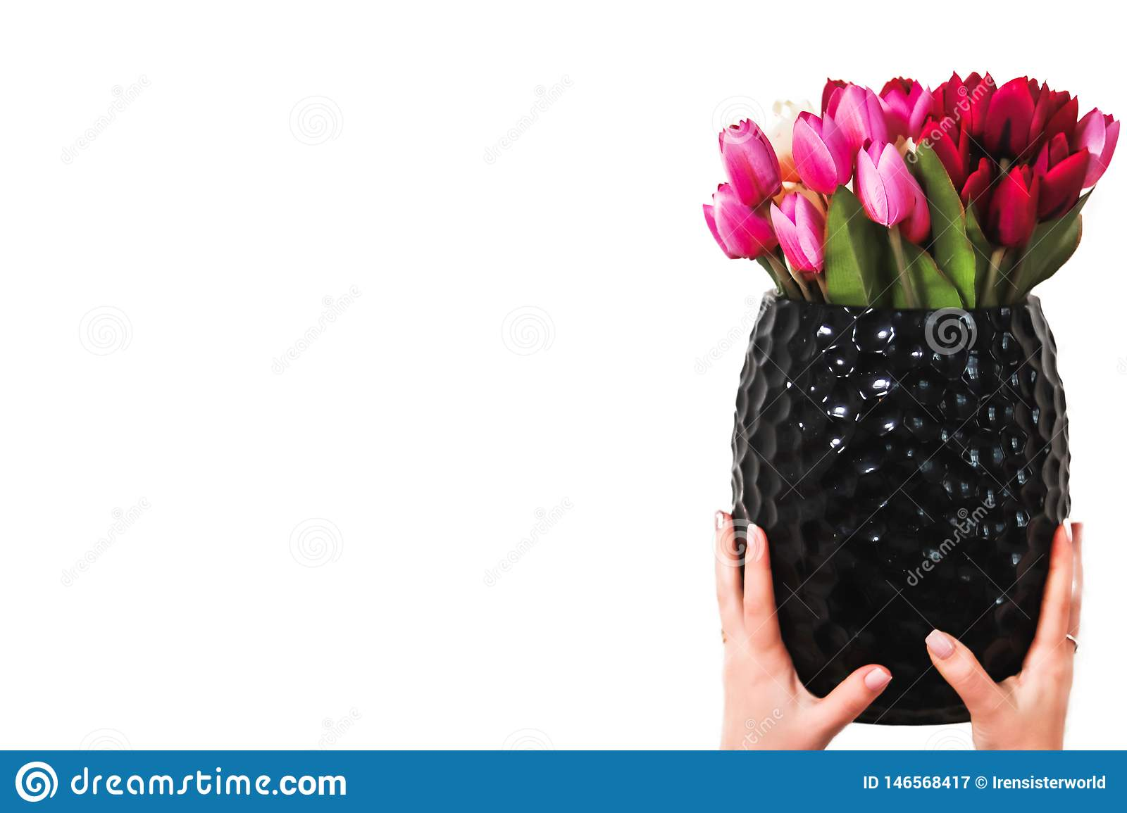 Hands holding a bouquet of flowers in a vase