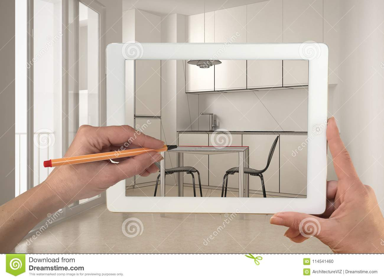 Hands holding and drawing on tablet showing real finished minimalist white kitchen. Modern kitchen in the background, architecture