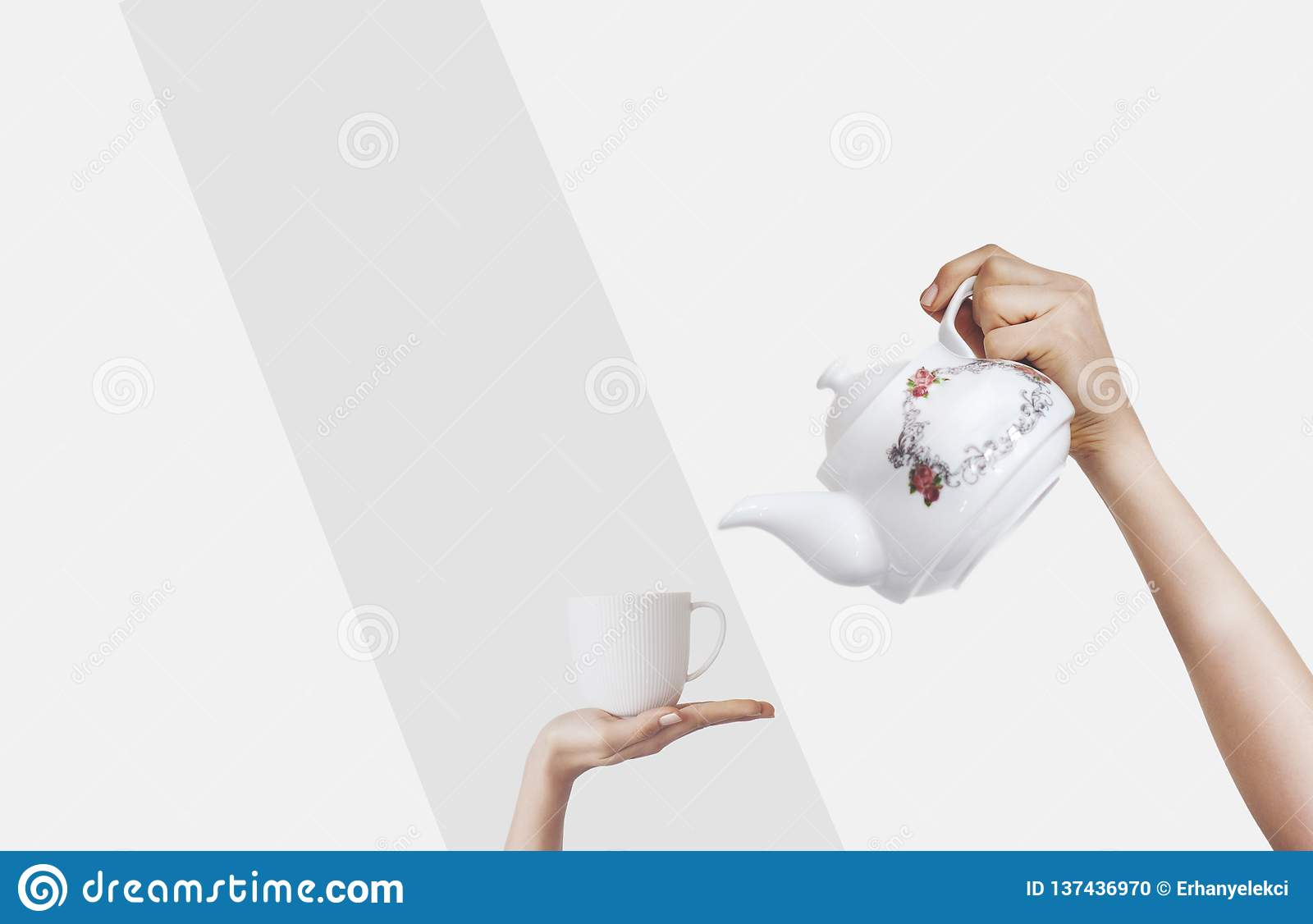 Hands holding kettle on isolated background and teacup