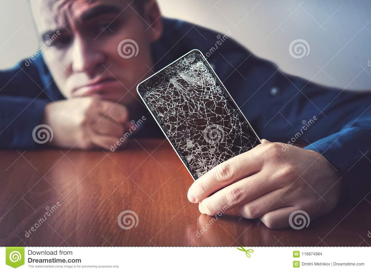 Hands holding a mobile phone with a broken screen over the wooden surface