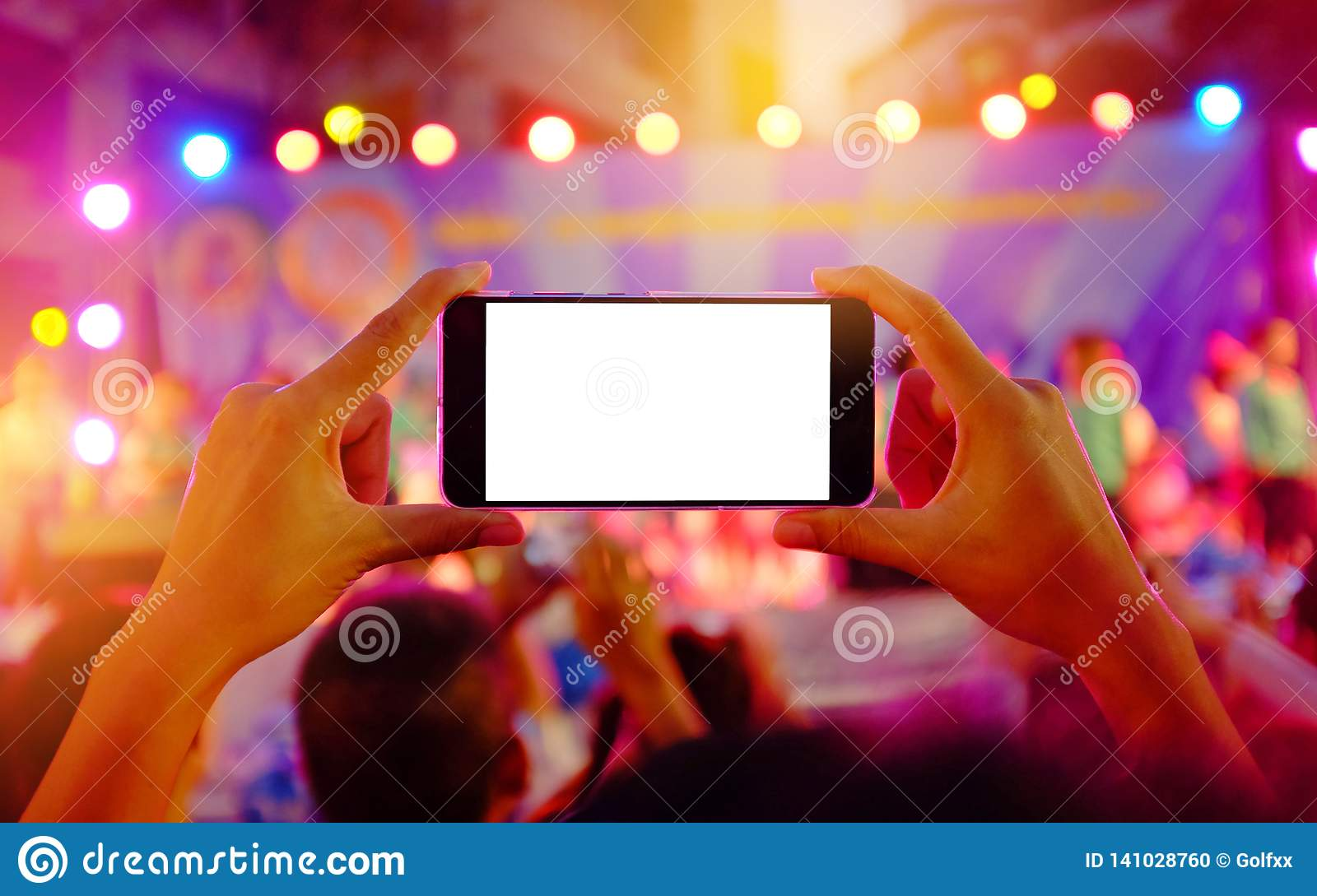 Hands holding a mobile smartphone records colorful live concert with blank white screen