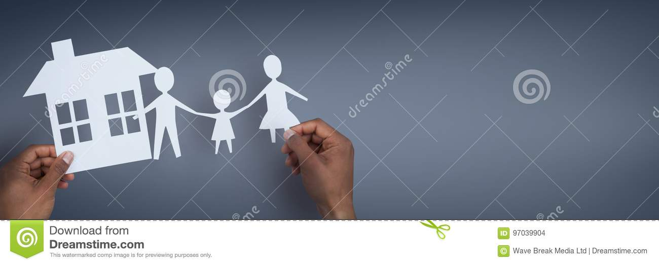 Hands holding paper figures against blue background as house and family insurance concept