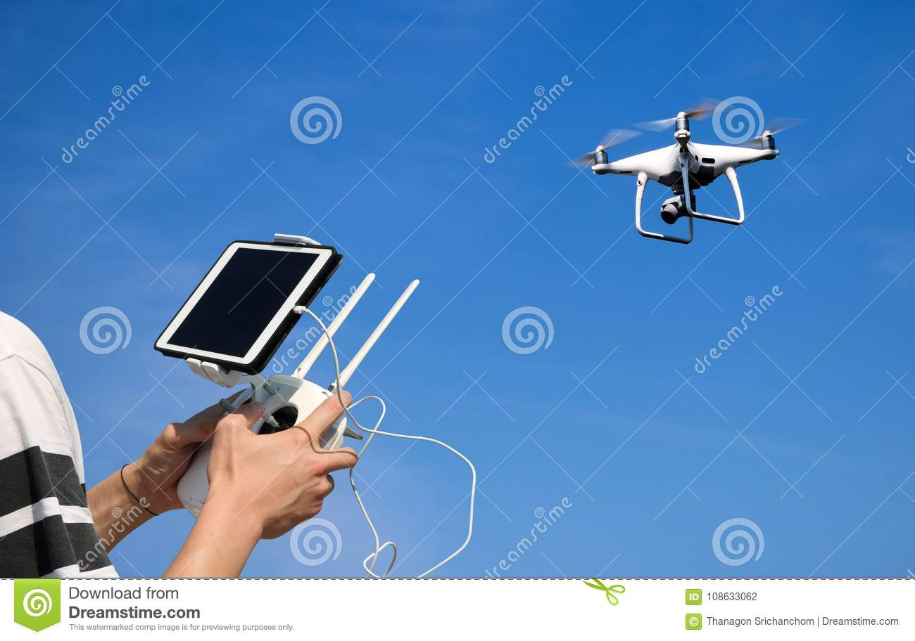 Hands holding a remote control drone camera while flying in the