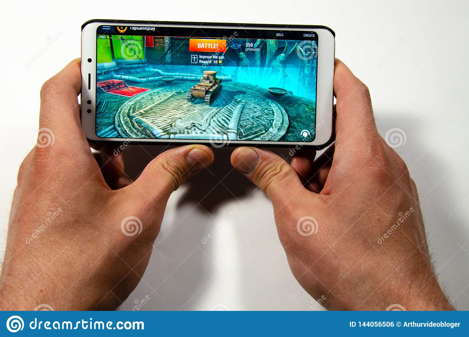 Hands holding a smartphone on which the game, gameplay Gameplay World of Tanks Blitz