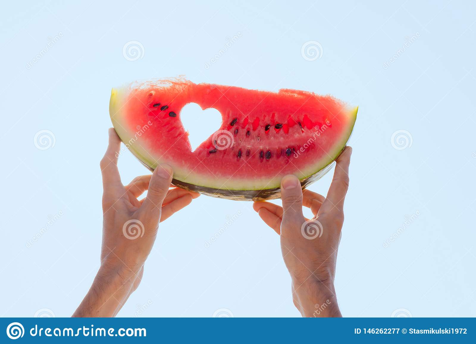 Hands holding a watermelon slice with heart center towards the sky