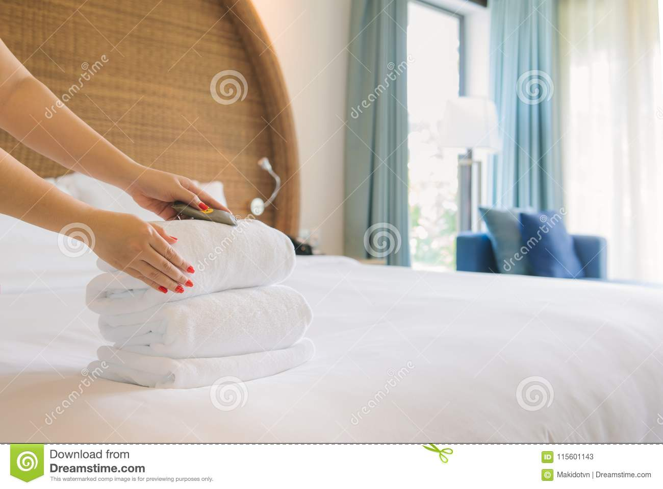 Hands of hotel maid bringing fresh towels to the room