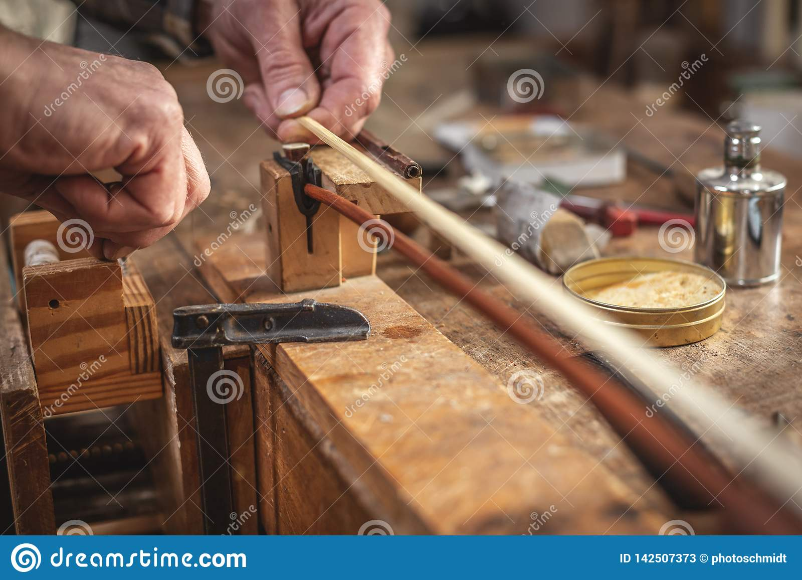 Violin maker working on a violin bow