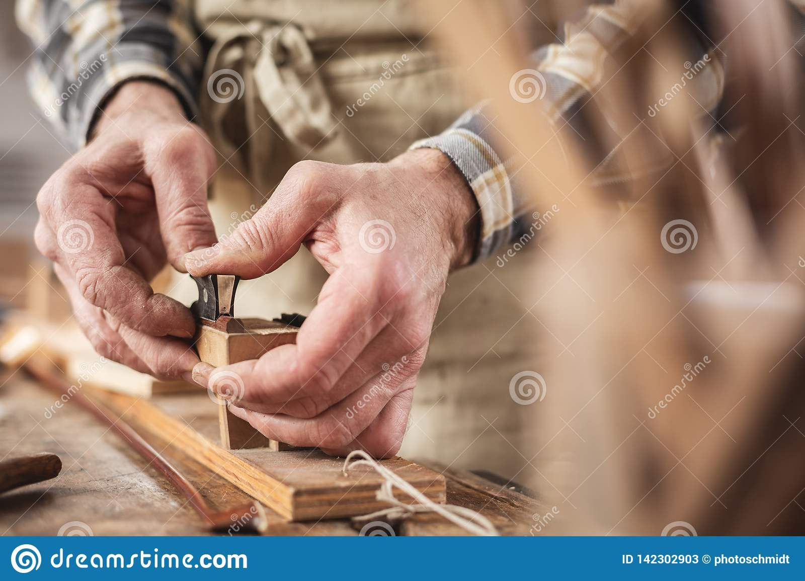 Hands of an instrument maker working on a violin bow