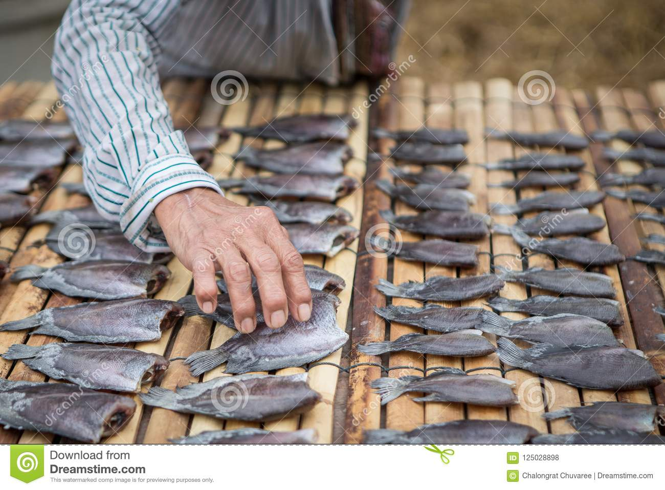 The hands keep the fish dry on a bamboo mat