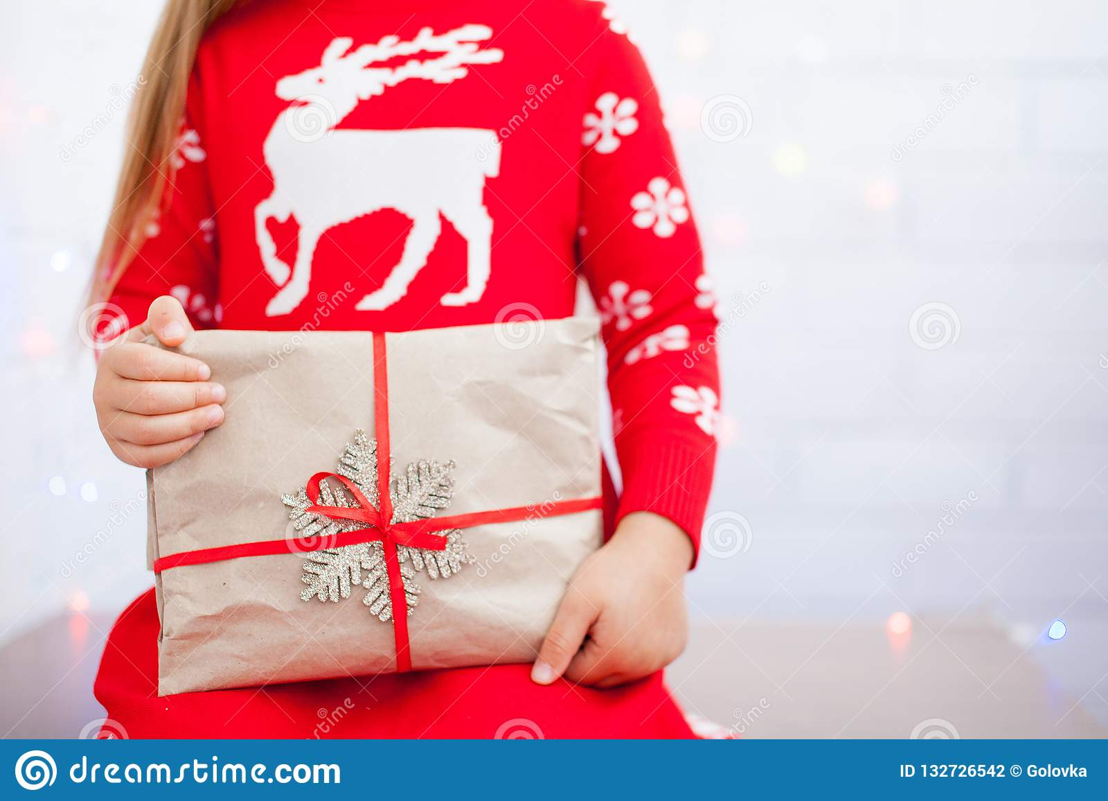 Hands of little girl is holding Christmas gift