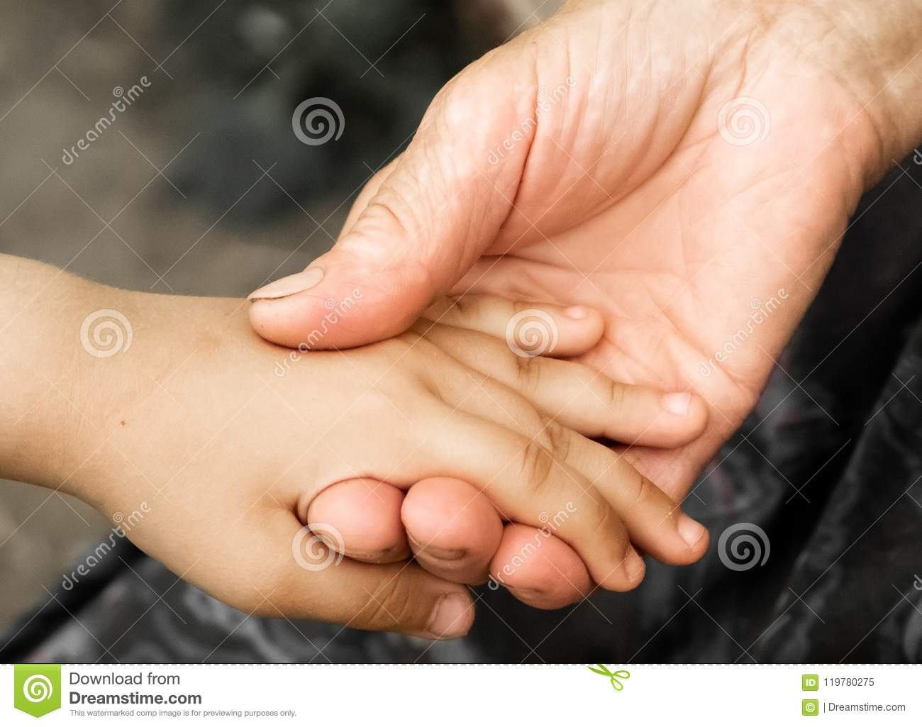 Hands of a little girl and an old grandmother. Hands of a little kids holding elderly man, World Kindness Day concept