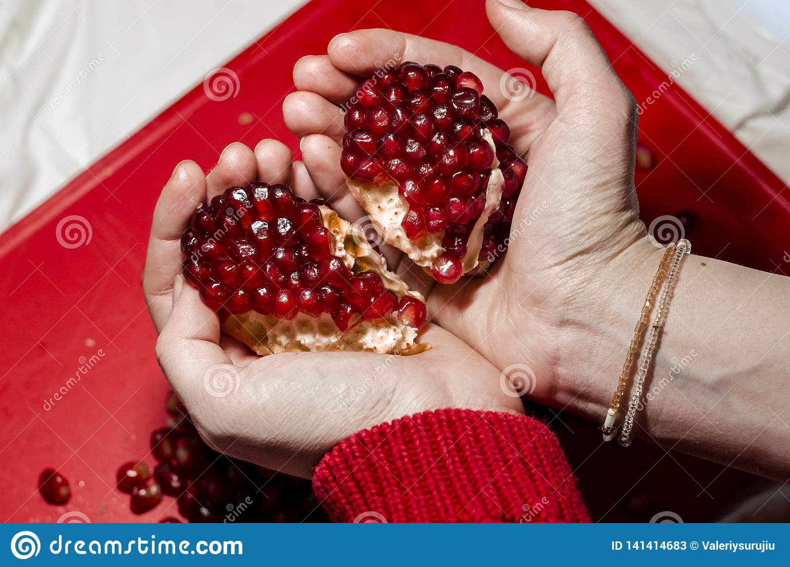 Hands making a heart of pomegranate pieces on the red cutting board