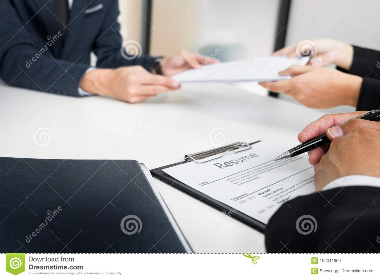 Hands of man giving application portfolio to HR man in office for interview.
