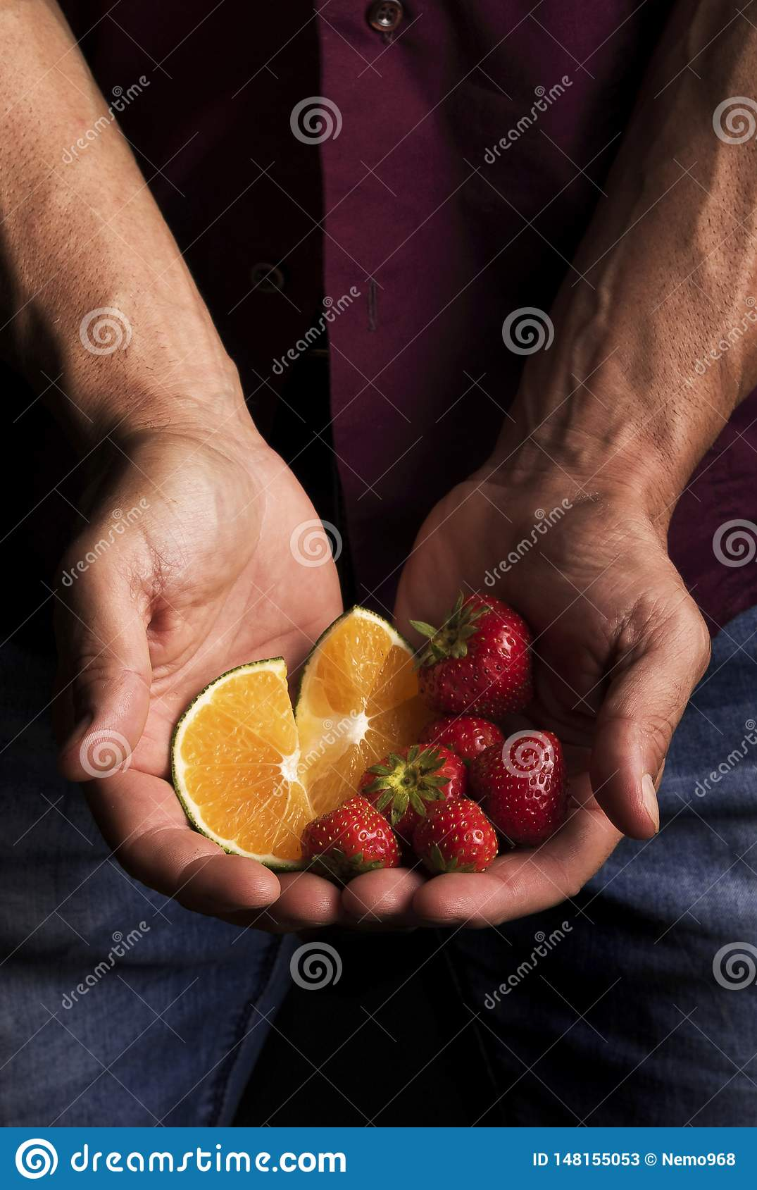 Hands of a man holding fruit