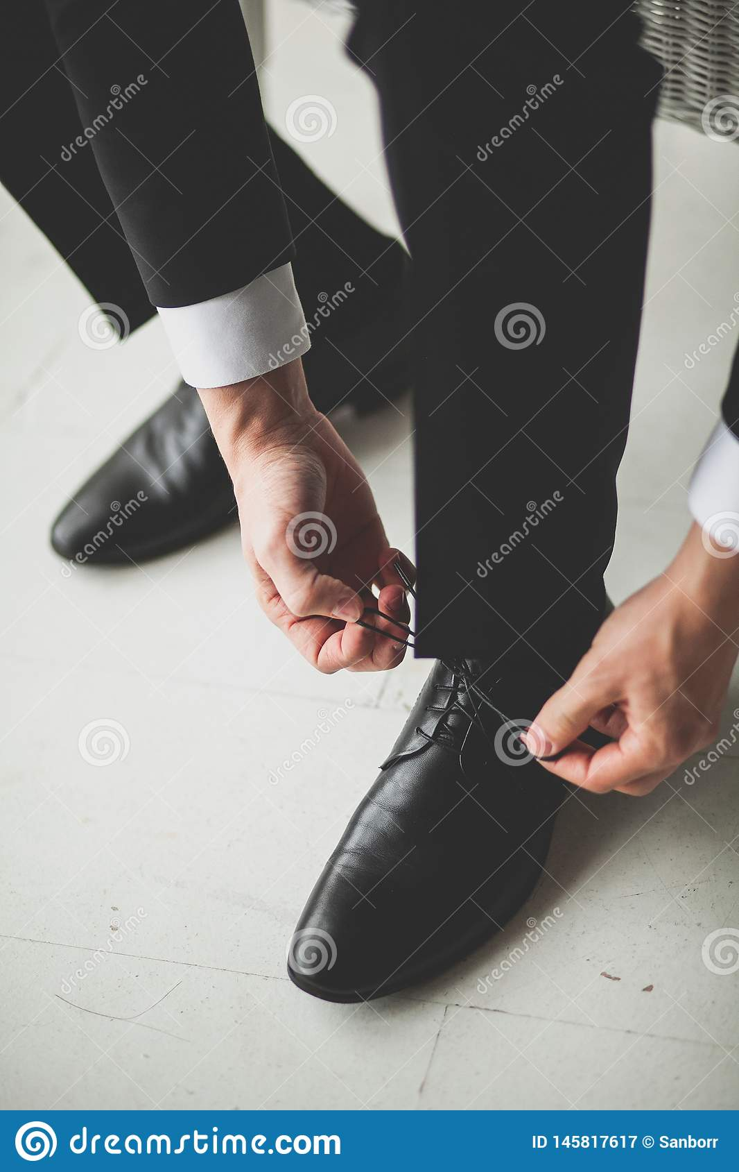 Hands men, groom, businessman tying the laces of his new black leather business shoes, close-up. The concept of business,