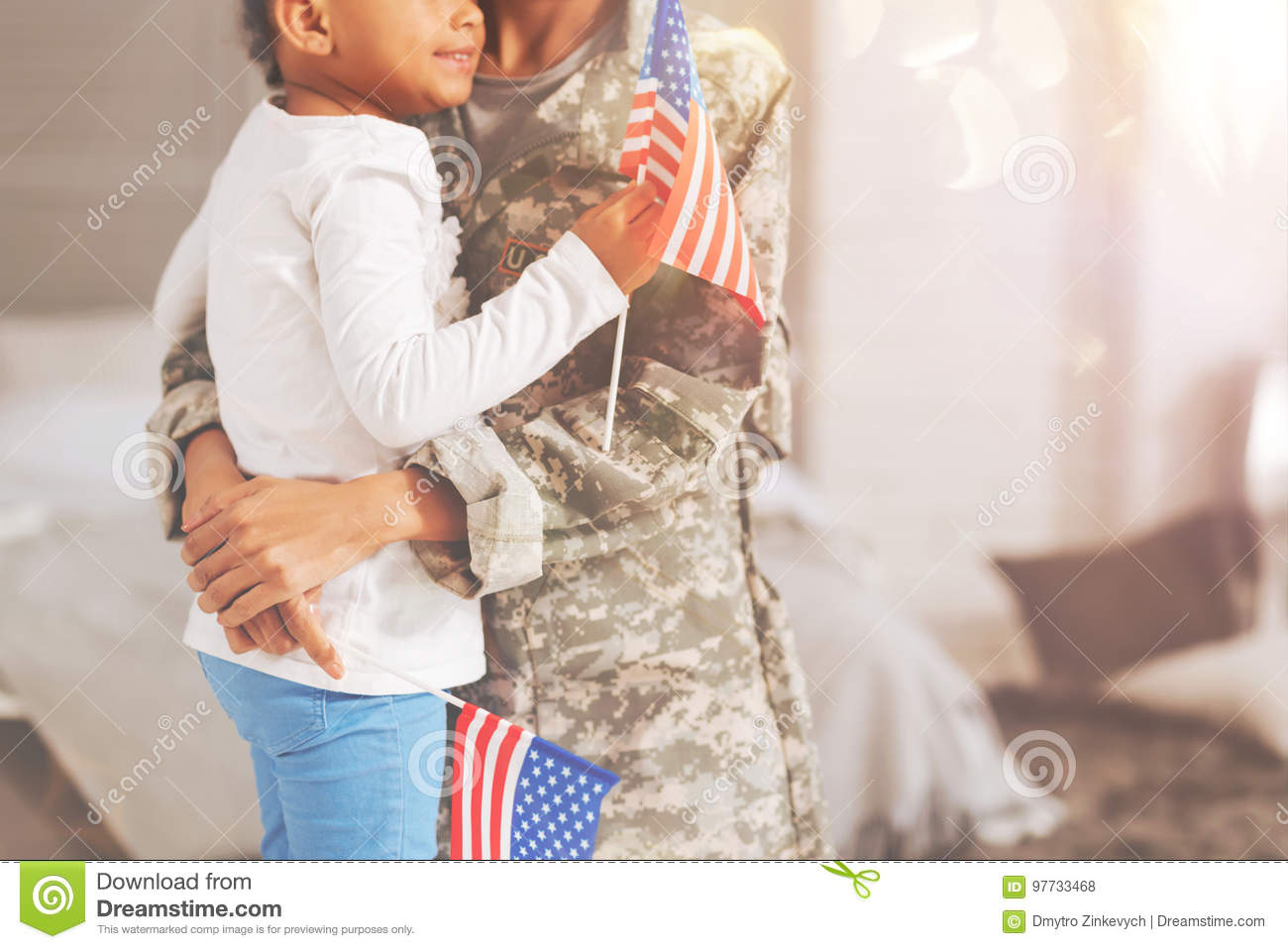 The close up of delicate female hands of a women in a military uniform  hugging her chubby daughter with an American flag her hand while the mother  holding ...