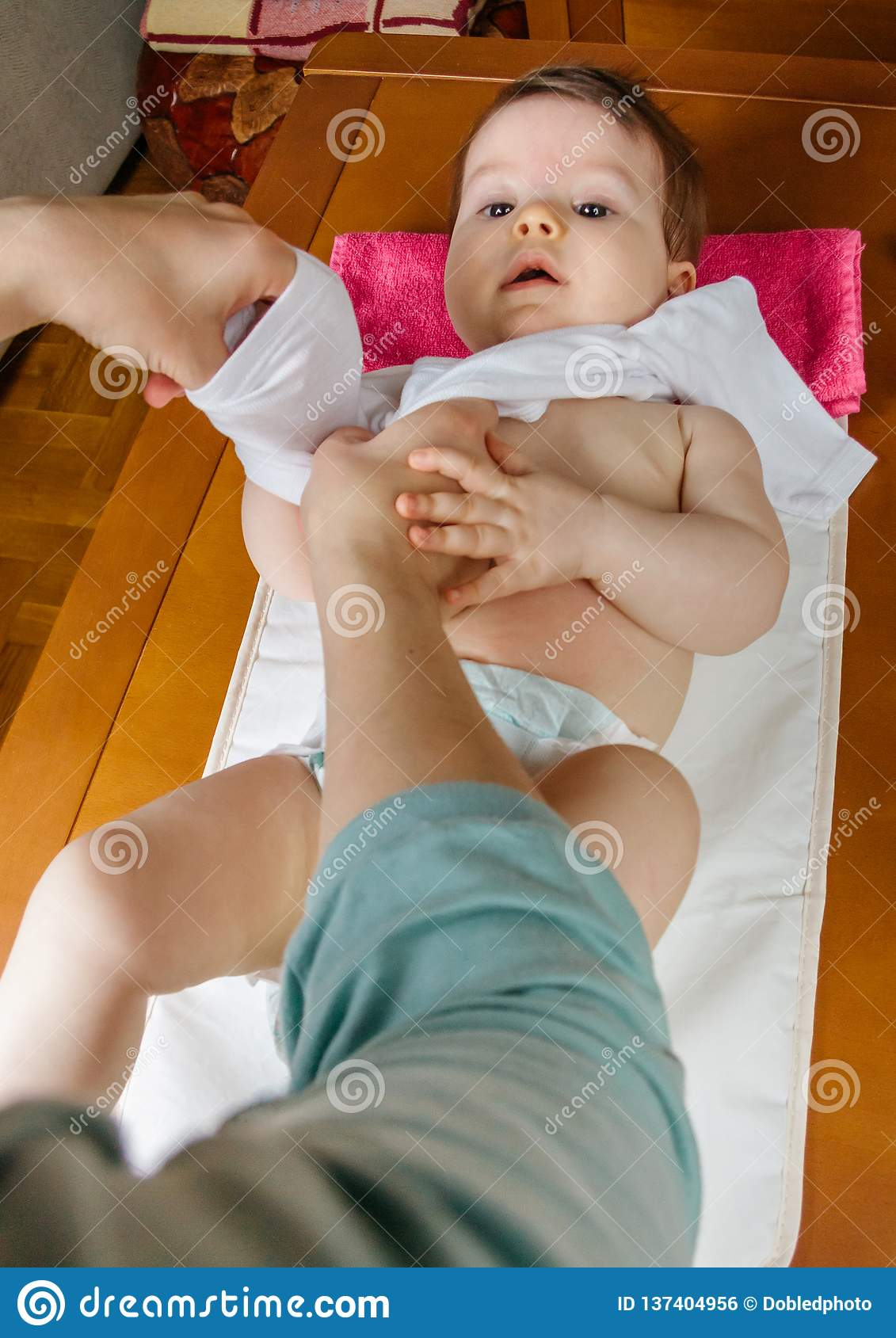 Hands of mother dressing her baby lying