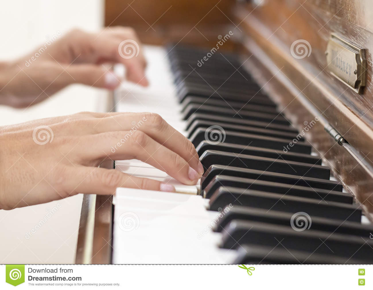 Hands of a musician playing a vintage wooden piano