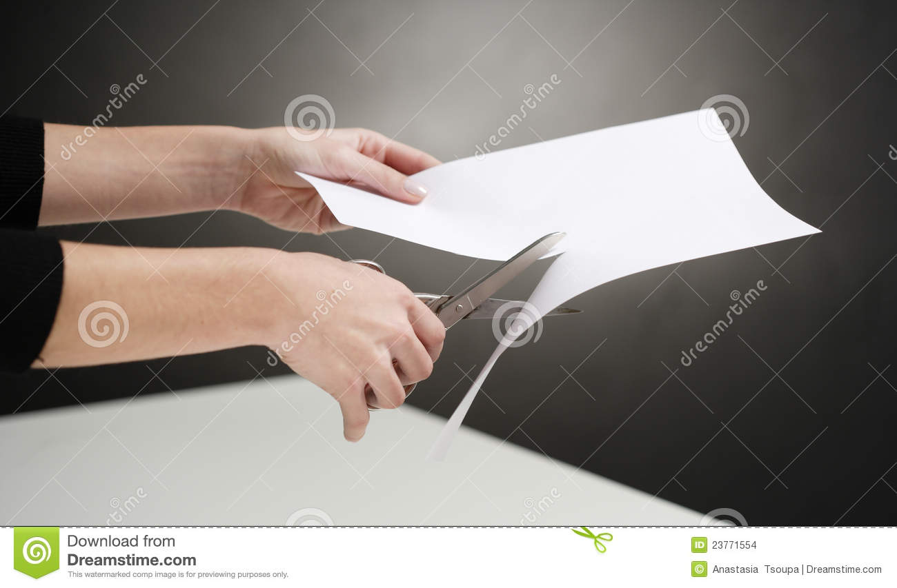 Hands of woman cutting white paper over table, black background.