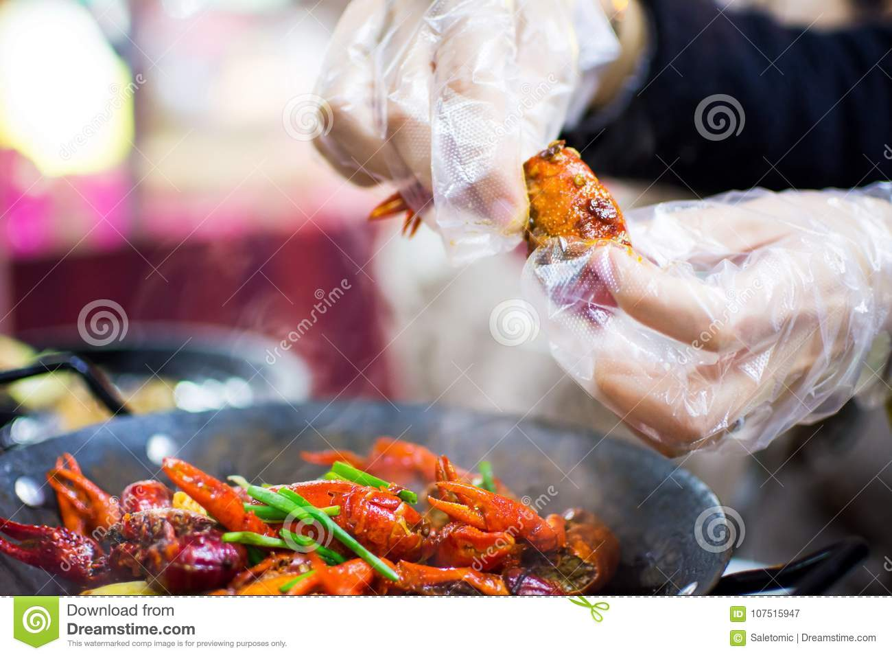 Hands with plastic gloves taking crayfish from spicy crayfish po