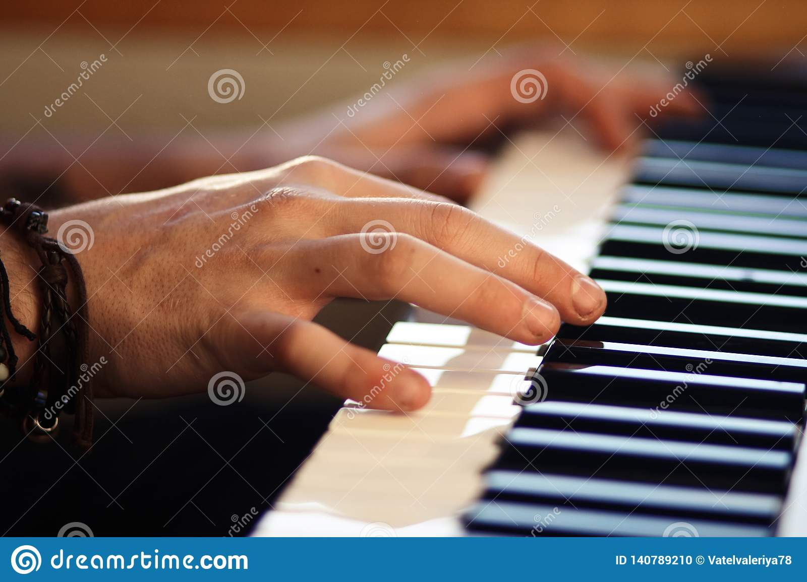 Hands playing a melody on a keyboard musical instrument
