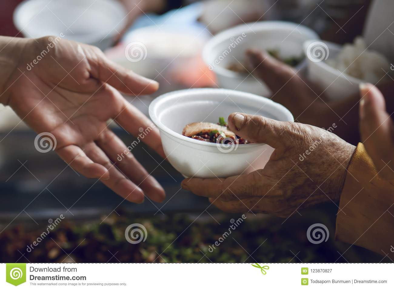 Hands of the poor receive food from the donor`s share. poverty concept