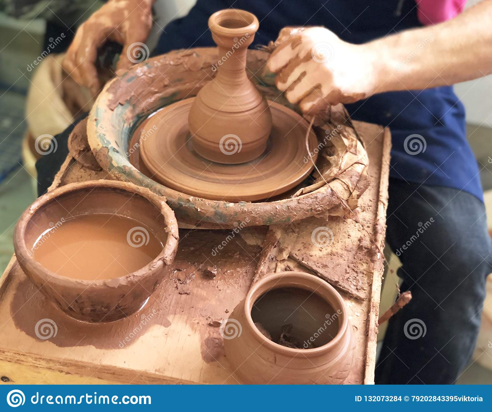 The hands of the Potter who makes the dishes from brown clay