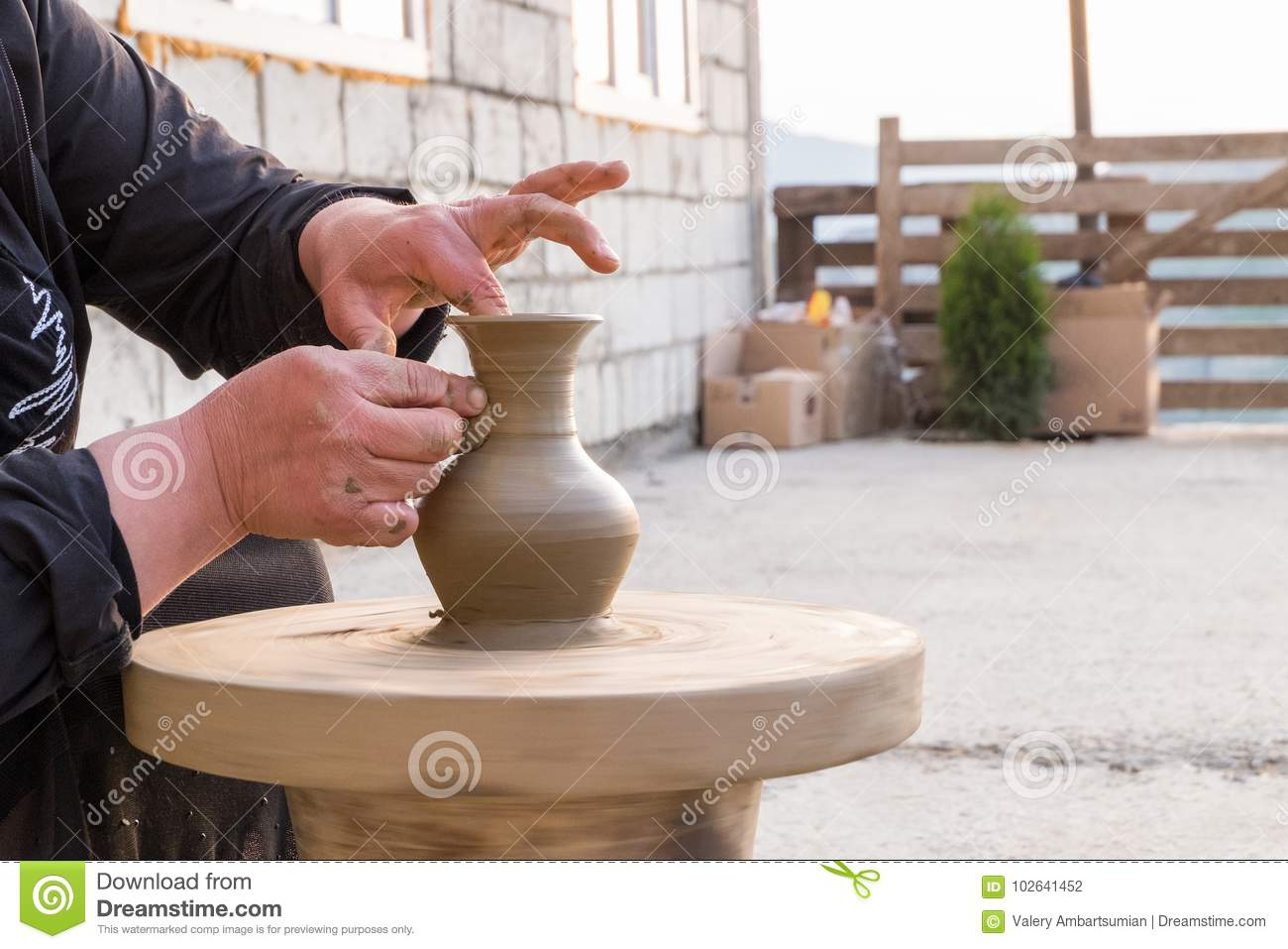 Hands of a potter woman make a pitcher of clay in the courtyard of the house
